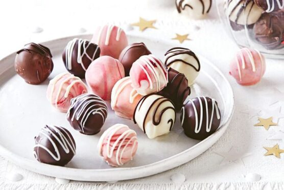 Chocolate coated truffles in pink, white, and brown colors