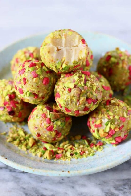 White chocolate truffles coated with chopped pistachios and raspberries
