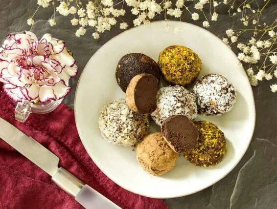 Keto truffles coated with cocoa powder, shredded coconut, and crushed pistachios