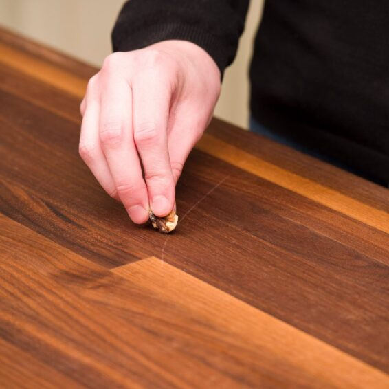 Rub a pecan nut on a scratched wooden surface
